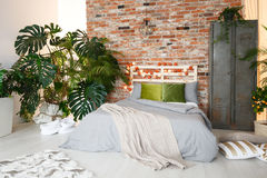 Bed, locker and monstera. King-size bed, metal locker and monstera in modern bedroom with brick wall stock photo