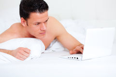 Bed lying person with computer Royalty Free Stock Images