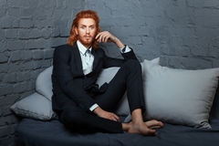 On the bed a man with freckles and red hair. Stock Photos