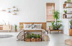 Bed met houten hoofdeinde in wit ruim slaapkamerbinnenland met kast en installaties Echte foto stock fotografie