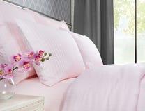 Bed met roze bedlinnen tegen een venster met grijze gordijnen royalty-vrije stock afbeelding