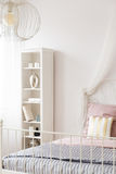 Bed with metal frame. White bedroom with bed with metal frame, lamp and bookcase Royalty Free Stock Image