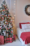 Bed next to the Christmas tree. Interior with a bed next to the Christmas tree Royalty Free Stock Image
