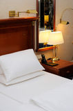 Bed and night table in a hotel room Stock Photography