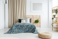 Bed with patterned blue coverlet royalty free stock photo