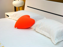 Bed and pillow. On the bed has a heart pillow Stock Photos