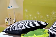 Bed and pillow in bedroom for kids. With lamp and toys on night table, shown as children's room interior and living environment Royalty Free Stock Images