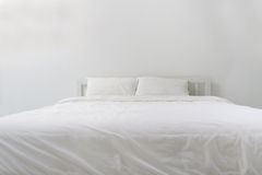 Bed with  pillow and blankets in white bedroom. Bed with white pillow and blankets in white bedroom Royalty Free Stock Photography