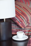 Bed with a pillow and a cup of tea. Bed with a pillow, a cup of tea on the bedside table and lamp Stock Photo