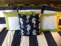 Bed With Pillows. Beautiful blue and white striped pillows with a pillow of blue and white sea horses Royalty Free Stock Photo