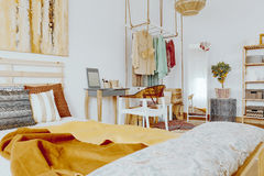 Bed with pillows and blanket. Wooden king-size bed with decorative pillows and blanket in sandy colors Royalty Free Stock Photo
