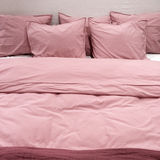 Bed with pink bedclothes Stock Photos