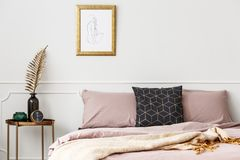 Bed with pink bedding. Framed sketch hanging above bed with dirty pink bedding and black cushion with golden pattern in bedroom interior Royalty Free Stock Image
