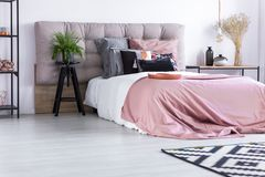 Bed with pink quilt cover. Copper decorations on rack in cozy simple apartment with patterned pillows on bed with pink quilt cover stock photography