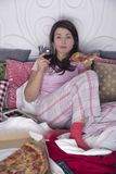 In bed with pizza and wine. Lonely evening of spinster in bed with pizza and wine royalty free stock photography