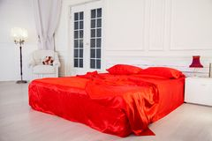 Bed with red sheets in white bedroom Interior. 1 Royalty Free Stock Images