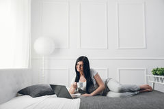 bed relaxing Όμορφη γυναίκα που απολαμβάνει ένα φλιτζάνι του καφέ και που χρησιμοποιεί το lap-top της Στοκ εικόνες με δικαίωμα ελεύθερης χρήσης