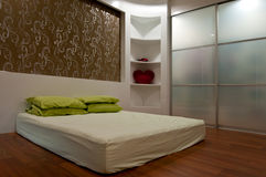 Bed room. Contemporary bed room with timber flooring, wall paper and walk in wardrove Royalty Free Stock Photography