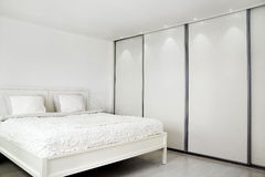 Bed-room. Bed and a closet. A picture of a bedroom, with a bed and a wall-closet royalty free stock photography