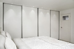 Bed-room. Bed and a closet. A picture of a bedroom, with a bed and a wall-closet royalty free stock photos