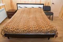 Bed in the room. The big bed is made by a cover costs in the room Royalty Free Stock Images