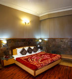 Bed room home interior design. Bedroom and home interior design. A beautiful wooden bed in a room with beautifully tiled walls and night lighting Royalty Free Stock Photo