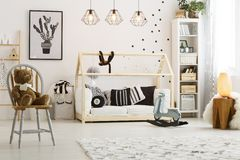 Bed in the room. Modern designed wooden bed for baby in cozy spacious room Stock Photos