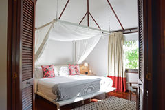 Bed room of a modern wooden house hotel in tropical country Royalty Free Stock Photo
