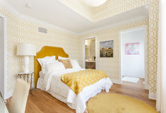 Bed room. A view of a comfortable bed room with a soft bed and warm lighting Royalty Free Stock Photos