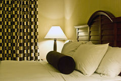 Bed settings. Comfortable bed settings with fluffy pillows and fresh linens Stock Image