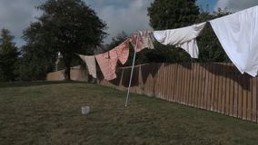 Bed sheets drying outside in the wind stock footage