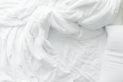 Bed sheets and pillows messed up after nights sleep ,comfort and bedding in a hotel room, concept travel and vacation. Bed sheets and pillows messed up after stock photos