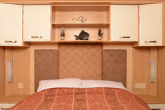 Bed with shelves and cabinets. Bed with built-in shelves and overhead storage cabinets Royalty Free Stock Photography