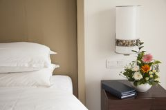 Bed and side table in a Hotel room. With fresh flowers, note pad,m and TV remote stock photos