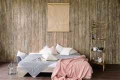 Bed for sleeping in the room. A wooden wall. Cozy and comfortabl royalty free stock photos