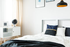 Bed and small book shelf. Modern bed and white small book shelf stock image