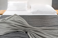Bed with striped cover and white pillows Royalty Free Stock Image