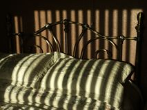 Bed, with sunlight creating broad stripes of shadow. stock photos