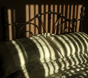 Bed, with sunlight creating broad stripes of shadow. stock photography