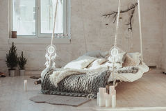 The bed suspended from the ceiling. Grey big cozy blanket knit. Scandinavian style, gray plaid, candles. Stock Photos