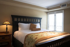 Bed with table and lamp Royalty Free Stock Photo
