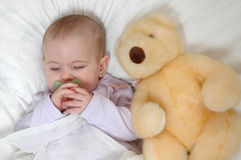 Bed Time. Darling baby sleeps on white comforter with a teddy bear next to her. Sleepy little baby Stock Photo