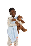 Bed Time. Young African American boy wearing pajamas and holding a blue blanket and a well-loved teddy bear. Isolated on a white background Royalty Free Stock Images