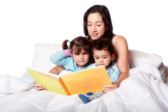 Bed time story book. Mother reading bed time story book to daughter and son kids in bed, isolated Royalty Free Stock Images