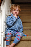 Bed time toddler. A tired toddler boy sitting on the stairs wearing half of his pajamas Stock Image