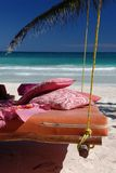 Bed on tropical beach. Bed suspended from palm tree on tropical beach Royalty Free Stock Photography