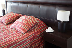 Bed with two pillows and a cup of tea Royalty Free Stock Photo