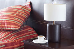Bed with two pillows and a cup of tea. Bed with a pillow, a cup of tea on the bedside table and lamp Stock Photography