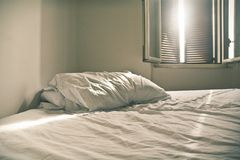 A bed unmade with white sheets on a Sunday afternoon stock image