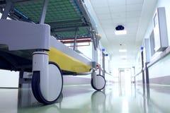 Bed on wheels waiting in the illuminated hospital corridor Stock Image